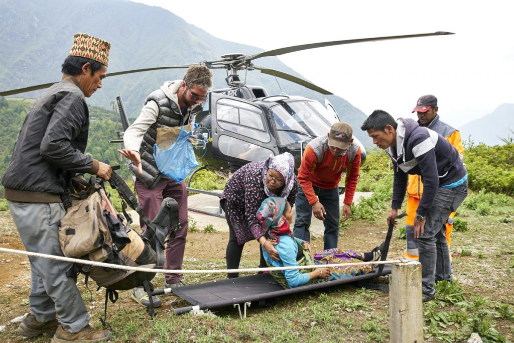 British doctor Alexander Kumar and Lakpa Sherpa assist a local elderly lady suffering from servere stomach pains at Lukla hospital helipad. Rescue flight flown by Manang pilot Ryan Skorecki.
